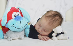 Newborn baby boy sleeping with his toys Stock Photography