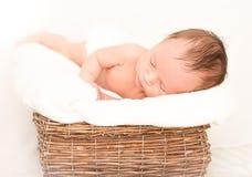 Newborn baby boy sleeping in old wicker basket covered by blanke Stock Image