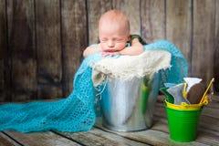 Newborn baby boy sleeping in a silver metal bucket Stock Image
