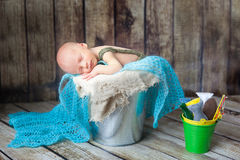 Newborn baby boy sleeping in a silver metal bucket Stock Images