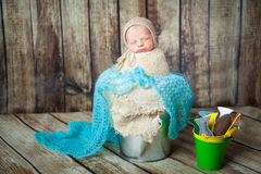 Newborn baby boy sleeping in a silver metal bucket Stock Photo