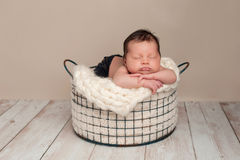 Newborn Baby Boy Sleeping in a Wire Basket. Three week old newborn baby boy wearing jeans and sleeping on his stomach in a wire basket. Shot in the studio on a Stock Photos