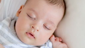 Newborn baby boy in striped clothes is sleeping. On a white bed stock video footage