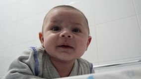 Newborn baby boy tree months old on his tummy on the baby changer smiling to camera stock footage
