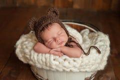 Newborn Baby Boy Wearing a Bear Bonnet. Four week old newborn baby boy wearing a brown crocheted bear hat. He is sleeping in a white, wooden bucket. Shot in the stock photo