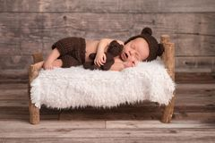 Newborn Baby Boy Wearing a Bear Bonnet. Two week old newborn baby boy wearing a brown, crocheted, bear bonnet. He is sleeping on a tiny, wooden bed and cuddling royalty free stock photography