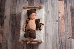 Newborn Baby Boy Wearing a Bear Bonnet. Two week old newborn baby boy wearing a brown, crocheted, bear bonnet. He is sleeping on a tiny, wooden bed and cuddling stock images