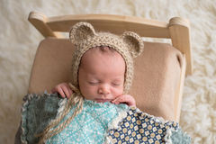 Newborn Baby Boy Wearing a Bear Bonnet. Two week old newborn baby boy wearing a tan, crocheted, bear bonnet. He is sleeping on a tiny, wooden bed and covered stock images