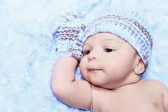 Newborn baby boy wearing a blue. A Closeup of the face of a tiny, newborn baby boy wearing a blue knit hat Stock Photo