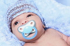 Newborn baby boy wearing a blue. A Closeup of the face of a tiny, newborn baby boy wearing a blue knit hat Stock Images