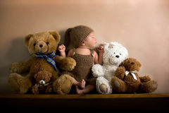 Newborn baby boy wearing a brown knitted bear hat and pants, sleeping on a shelf. Next to Teddy Bears. Shot in the studio on a creamy background, shot from stock photography