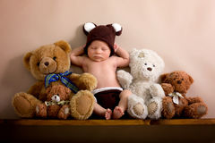 Newborn baby boy wearing a brown knitted bear hat and pants, sleeping on a shelf. Next to Teddy Bears. Shot in the studio on a creamy background, shot from stock photos