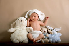 Newborn baby boy wearing a brown knitted rabbit hat and pants, s stock images