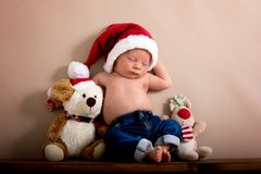 Newborn baby boy wearing a christmas hat and jeans, sleeping on Royalty Free Stock Photos