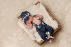 Newborn Baby Boy Wearing a Hat and Suspenders. Overhead shot of an eight day old newborn baby boy wearing a blue newsboy cap, suspenders and pants. He is Royalty Free Stock Photography