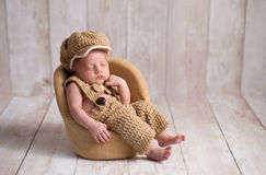 Newborn Baby Boy Wearing a Little Man Suit. Nine day old, newborn baby boy wearing a crocheted, little man suit with newsboy cap and bowtie. He is sleeping in a Stock Image