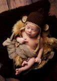 Newborn Baby Boy Wearing a Monkey Hat. A newborn baby boy wearing a crocheted monkey hat and sleeping in an antique wooden well bucket. Shot in the studio with a Royalty Free Stock Image