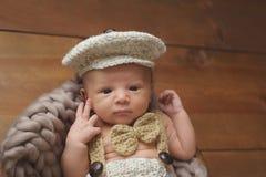 Newborn Baby Boy Wearing a Newsboy Cap and Bowtie Stock Image