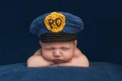 Newborn Baby Boy Wearing a Police Hat Stock Image
