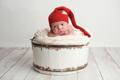 Newborn Baby Boy Wearing a Red Stocking Cap. Portrait of a two week old, alert, newborn baby boy with a cute expression. He is posed in a white bucket with his Stock Images