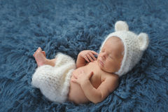 Newborn Baby Boy Wearing a White Bear Costume. Three week old newborn baby boy wearing a white, crocheted, bear bonnet and shorts. He is sleeping on his back on royalty free stock photos
