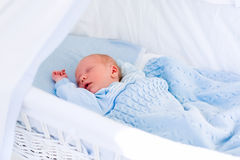 Newborn baby boy in white bassinet Stock Images