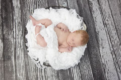 Newborn baby boy in white bowl against wooden background Royalty Free Stock Photography