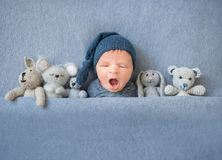 Newborn baby boy yawning and lying between plush toys