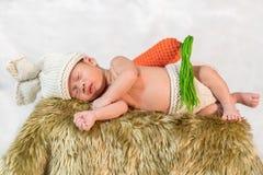Newborn baby in bunny costume sleeping on fur bed stock photos