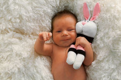 Newborn baby and bunny sock toy Stock Images
