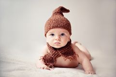Newborn baby in a cap and scarf. Newborn baby in cap and scarf looking into the camera Stock Photos