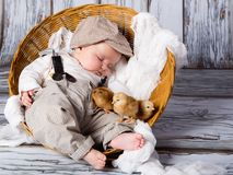 Newborn baby with chicks. Three chicks and a cute sleeping little newborn baby in wicker basket Stock Images