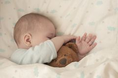 Newborn baby child asleep hugging a bear. Sleeping baby girl boy hid his nose in a teddy bear. Close-up soft focus. Baby portrait stock photography