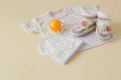 Newborn baby clothes and shoes on beige background Stock Image