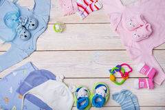 Newborn baby clothes. On wooden background stock images
