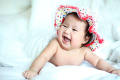 Newborn Baby with Colorful Floppy Hat Lying Down on a White Blan Royalty Free Stock Photos