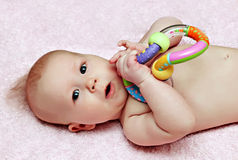 Newborn baby with colorfull rattle Royalty Free Stock Photography