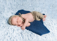Newborn baby in costume lying on blue blanket Royalty Free Stock Image