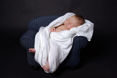 Newborn baby on couch. 11 days old newborn baby boy sleeping on a mini couch Royalty Free Stock Photos