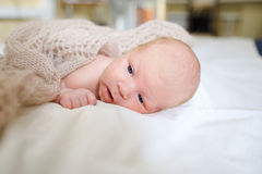 Newborn baby covered knitted blanket and lying on bed in sleepin Royalty Free Stock Photography