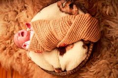 Newborn baby covered in knitted scarf cries Stock Images
