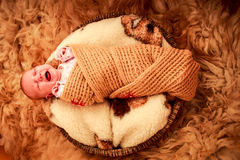 newborn baby covered in knitted scarf cries Stock Photo