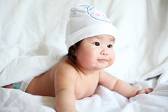 Newborn Baby with Cow Hat Lying Down on a White Blanket Stock Photography