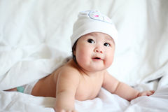 Newborn Baby with Cow Hat Lying Down on a White Blanket Royalty Free Stock Photography