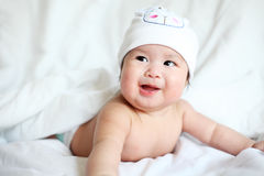 Newborn Baby with Cow Hat Lying Down on a White Blanket Stock Photo