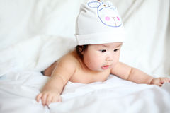 Newborn Baby with Cow Hat Lying Down on a White Blanket Royalty Free Stock Photos