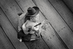 Newborn Baby Cowboy Playing a Tiny Guitar Royalty Free Stock Photo