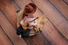 Newborn Baby Cowboy Playing a Tiny Guitar. A three week old baby boy wearing a cowboy hat and jeans and playing a tiny acoustic guitar. His lips are pursed, as stock photo