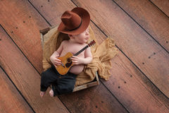 Newborn Baby Cowboy Playing a Tiny Guitar. A three week old baby boy wearing a cowboy hat and jeans and playing a tiny acoustic guitar. He is lying in a wooden royalty free stock photography
