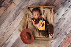Newborn Baby Cowboy Playing a Tiny Guitar. A two week old baby boy wearing crocheted overalls and playing a tiny acoustic guitar. He is lying in a wooden crate stock image